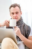 stock photo of rhinitis  - Ill man suffering from rhinitis sitting on the couch at home - JPG