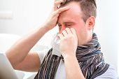 picture of rhinitis  - Ill man suffering from rhinitis sitting on the couch at home - JPG