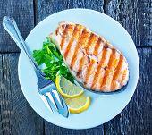 pic of salmon steak  - grilled salmon steak with lemon on white plate - JPG