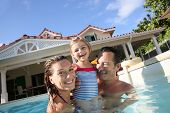 foto of swimming pool family  - Family playing in swimming pool of private villa - JPG