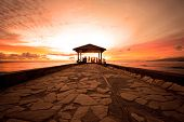 stock photo of waikiki  - Golden hour sunset at a cement rock pier at Waikiki Beach - JPG