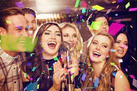 image of karaoke  - Happy friends singing karaoke together against flying colours - JPG