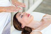 foto of reiki  - Calm woman receiving reiki treatment in the health spa - JPG