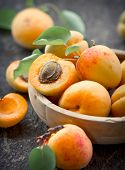 image of apricot  - Apricots ripe and healthy in the wooden bowl on the table close up - JPG