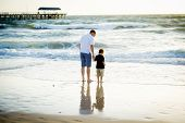 pic of barefoot  - young happy father holding hand of little son walking together on the beach with barefoot in sand in front of sea waves the kid smiling and having fun with dad in Summer sunset coast - JPG