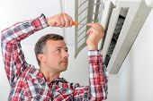 stock photo of air conditioning  - Man repairing his air conditioning system - JPG