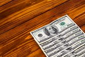 stock photo of american money  - Wooden table with money american hundred dollar bills in symmetrical rows - JPG