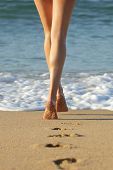 picture of nudism  - Long perfect woman legs walking on the sand of the beach towards the sea leaving footprints - JPG