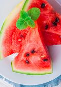 picture of watermelon slices  - sliced watermelon with mint leaf on a white plate - JPG