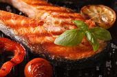 stock photo of salmon steak  - Grilled red fish steak salmon macro and vegetables on the grill - JPG