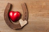 foto of horseshoe  - Red heart and a horseshoe on a wooden board - JPG