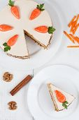 stock photo of sponge-cake  - Sliced homemade carrot sponge cake with cinnamon and walnut on white background - JPG