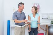 stock photo of crutch  - Woman using crutch and talking with her doctor in medical office - JPG