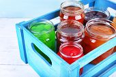 stock photo of wooden crate  - Homemade jars of fruits jam in crate on wooden table and color wall background - JPG
