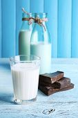 stock photo of bittersweet  - Glass and bottles of milk with chocolate chunks on color wooden planks background - JPG