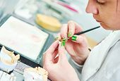 stock photo of prosthesis  - Dental technician painting tooth during work on dentures at prosthesis laboratory - JPG