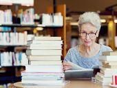 stock photo of elderly  - Elderly lady reading books in library - JPG