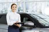 picture of showrooms  - Young pretty woman dealer in showroom standing near car  - JPG