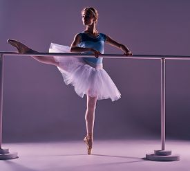 foto of ballet barre  - classic ballet dancer in white tutu posing on one leg at ballet barre on a lilac background - JPG