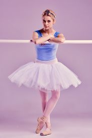 picture of ballet barre  - classic ballet dancer in white tutu at ballet barre on a lilac background - JPG