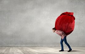 picture of heavy bag  - Young man in casual carrying heavy red bag - JPG