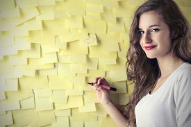 stock photo of post-teen  - Young woman writing something on a wall of post - JPG