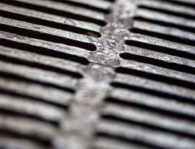 stock photo of grating  - Closeup of the metal drain grate surface - JPG