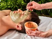 Mud facial mask of man in spa salon. Massage with clay full face. Girl on with therapy room. Man lyi poster