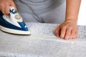 Housework And Household Concept. Man Is Ironing  White Curtain On Ironing Board At Home. Blue Iron I poster