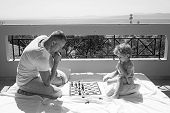 Father With Son On Balcony Play Chess. Child Play Chess With Father. Love And Trust As Family Values poster