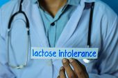 Doctor Holding A Card With Text Lactose Intolerance. Medical And Healthcare Concept. poster