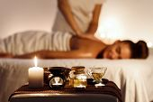 Aroma Spa. Woman Enjoying Massage In Luxury Spa With Candle On Foreground poster