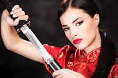 image of martial arts girl  - Pretty woman holding katana weapon on dark background - JPG