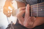 Young Mans Hands Playing Acoustic Guitar.the Guitar Is A Fretted Musical Instrument That Usually Ha poster