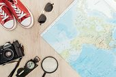 Top View Of Red Gumshoes, Film Camera, Magnifier, Compass, Sunglasses And World Map On Wooden Surfac poster