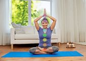 mindfulness, spirituality and yoga concept - happy woman meditating in lotus pose with seven chakra  poster
