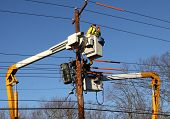 picture of lineman  - Two lineman working to restore power on electrical lines - JPG