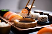 Closeup hand holding bamboo chopsticks with nigiri shrimp while soaking it in soy sauce. Detail of s poster
