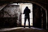 Prisoner Man Locked Up Standing In Old Underground Cellar , Silhouette From Behind Against Bars - Ca poster