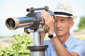 Постер, плакат: Старший мужчина глядя через телескоп