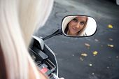 stock photo of crotch-rocket  - A pretty blonde woman looking into the mirror on her motorcycle - JPG