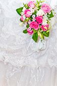 stock photo of pink rose  - beautiful wedding bouquet of pink roses against the white wedding dress background - JPG