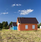 picture of hayfield  - Four bright multicoloured houses in the hayfield - JPG