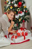 stock photo of shh  - Woman putting present box under Christmas tree and showing shh gesture - JPG