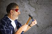 image of gad  - Construction worker wears safety glasses and holds hammer and gad tool - JPG
