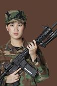 foto of military personnel  - Portrait of beautiful young US Marine Corps soldier with M4 assault rifle over brown background - JPG