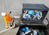 stock photo of garbage bin  - Worker of urban municipal recycling garbage collector truck loading waste and trash bin - JPG