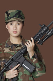 stock photo of united states marine corps  - Portrait of beautiful young US Marine Corps soldier with M4 assault rifle over brown background - JPG