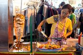 BANGKOK, THAILAND - JANUARY 9, 2012: Woman prepares traditional Thai food on Khao San Road food stal