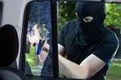 stock photo of thug  - Car thief with crowbar and broken glass - JPG
